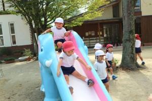 園児が滑り台で遊んでいる写真